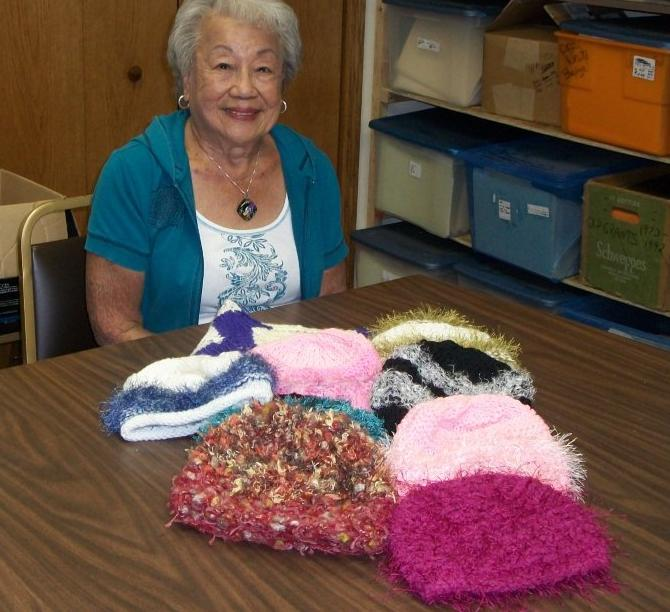 One of our home-based volunteers, Fung Scholz, with completed hats to be distributed this fall.