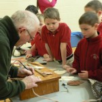 David Thill giving students his wood burning exhibit